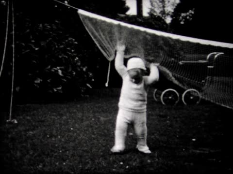 1932 boy walks under net, sits in leaves - 1932 stock videos & royalty-free footage
