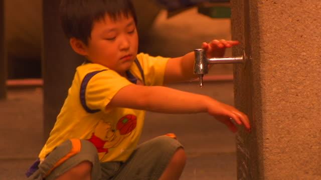 MS Boy washing hands at public fountain, Tokyo, Japan
