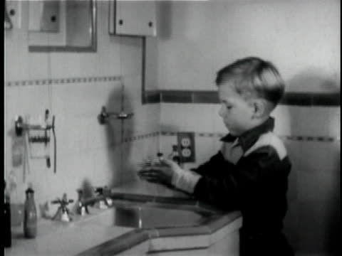 b/w ms pan boy washing hands in bathroom sink and wiping hands on towel / los angeles, california, usa - bathroom stock videos & royalty-free footage