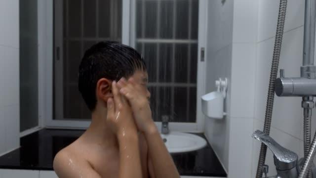 vídeos de stock e filmes b-roll de boy washing his face in bathroom - menino infancia pelado banheiro