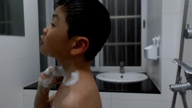 vídeos de stock e filmes b-roll de boy washing his neck with bath sponge indoors - menino infancia pelado banheiro