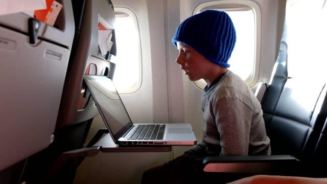 Boy horloges een film tijdens zijn vlucht