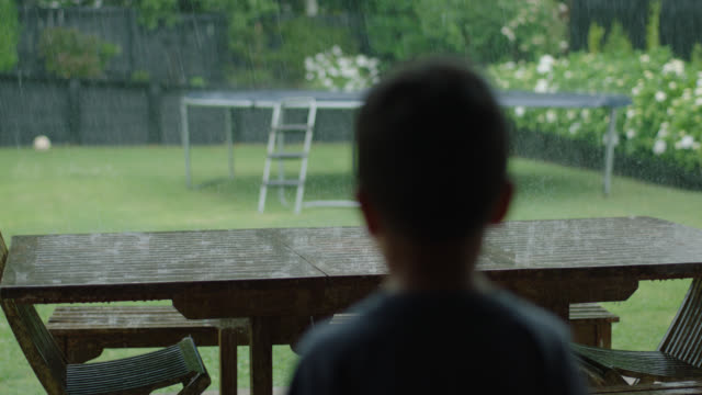 vídeos de stock e filmes b-roll de boy watches rain - tristeza
