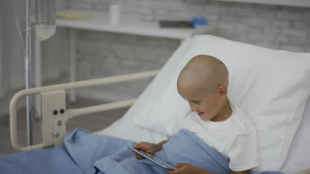 Garçon en regardant un comprimé dans un lit d'hôpital