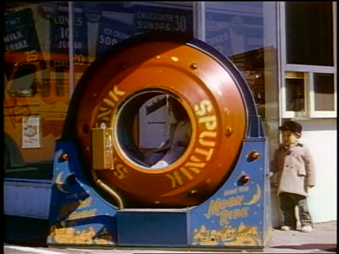 "1958 boy watching child in coin operated ""sputnik"" ride outdoors / newsreel - sputnik video stock e b–roll"