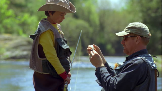 CU Boy (8-9) watching father putting bait on fishing hook, standing in river / Maine, USA
