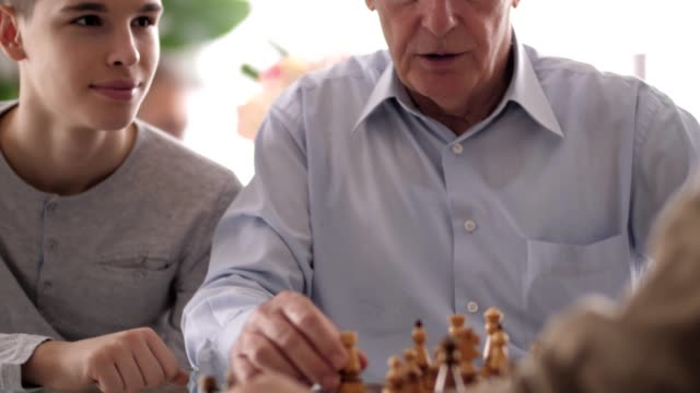 boy watching his grandfathers playing chess - nonno video stock e b–roll
