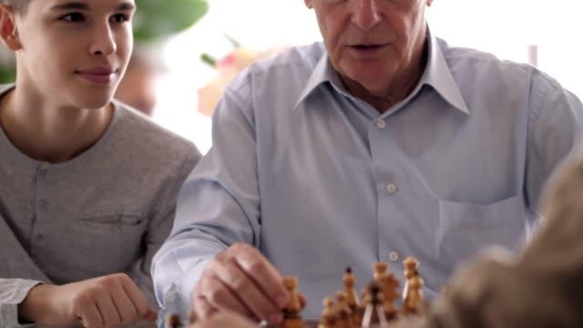 stockvideo's en b-roll-footage met jongen kijken naar zijn grootvaders spelen schaken - spelletjesavond