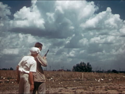 1946 boy watching man shoot clay targets with shotgun / clouds in background / AUDIO