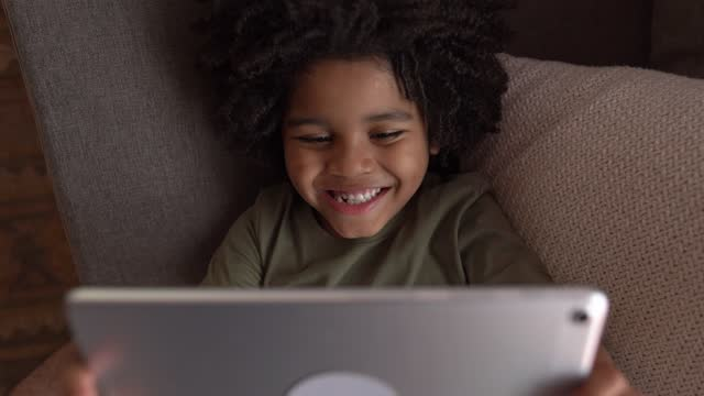 boy watching something on digital tablet at home - watching tv stock videos & royalty-free footage