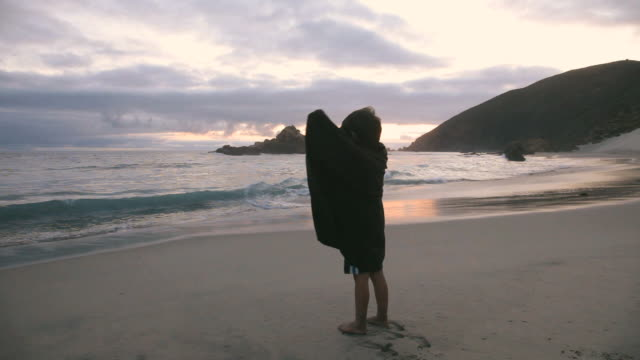 MS Boy (4-5) watching waves at beach wrapped in adult oversized shirt, Big Sur, California, USA
