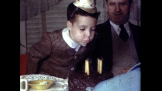 boy wearing a birthday hat and blows out his candles. - birthday stock videos & royalty-free footage