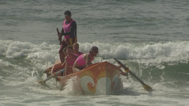 boy wearing a sun shirt with 'water safety' on the back stands with group on beach / life savers training boat sitting on the water with several... - pink shirt stock videos and b-roll footage