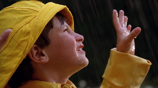 A boy wearing a yellow raincoat looks up at the rain.