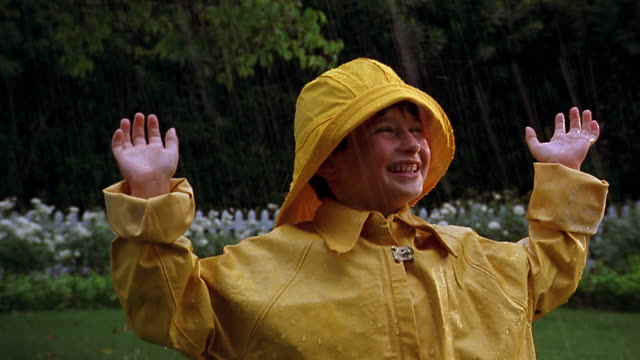 A boy wearing a yellow raincoat smiles and raises his arms in the rain.