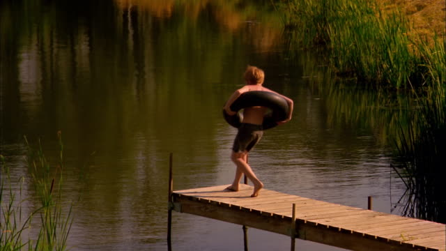 stockvideo's en b-roll-footage met a boy wearing an inner tube around his waist runs to the edge of a dock. - twijfel