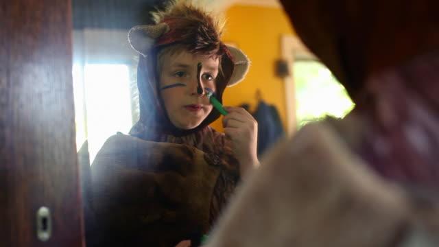 Boy wearing bear costume applying pace paint