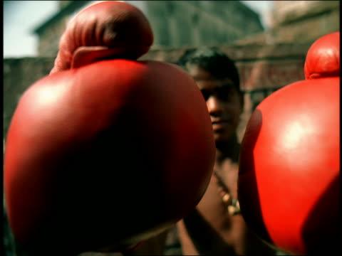 vídeos y material grabado en eventos de stock de soft focus ms boy wearing boxing gloves throwing punches at camera / varanasi, india - guante de boxeo