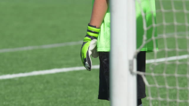 a boy wearing green gloves playing youth soccer football goalie goalkeeper on a turf grass field. - slow motion - goalkeeper stock videos & royalty-free footage