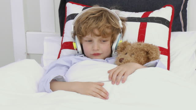 ms boy (6-7) wearing headphones lying in bed with teddy bear / cape town, south africa - teddy boy stock videos & royalty-free footage
