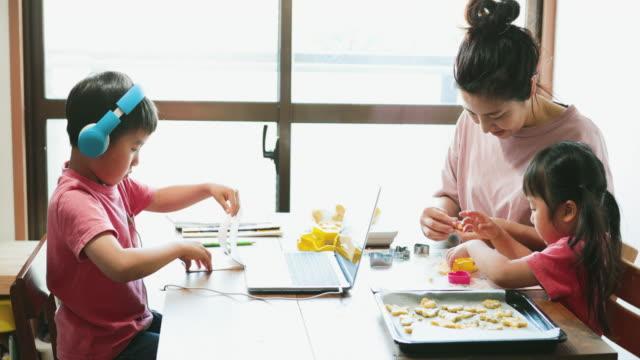 vidéos et rushes de garçon utilisant le casque prenant un cours d'e-learning avec la famille dans le salon - rester à la maison expression