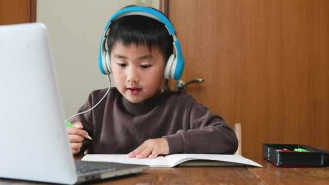 stockvideo's en b-roll-footage met jongen die hoofdtelefoon draagt die een e-het leren cursus met laptop neemt - e learning