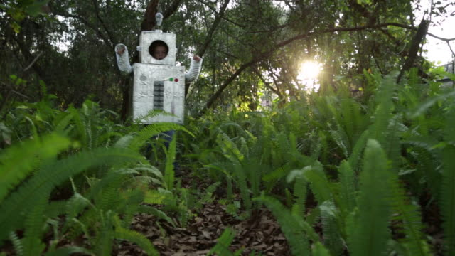 WS TS Boy wearing home made robot costume walking out of woods towards camera.