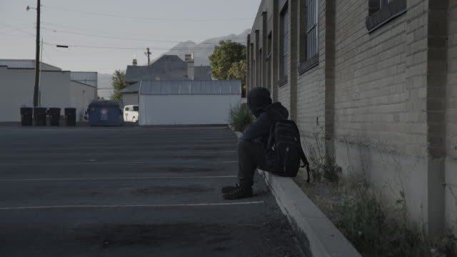 vidéos et rushes de boy wearing hooded sweatshirt sitting on curb in empty parking lot / provo, utah, united states - fragilité