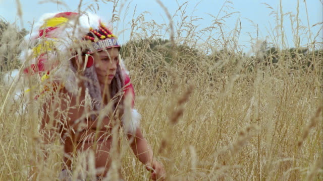 cu, boy (12-13) wearing indian costume playing in grass, saint ferme, gironde, france - headdress stock videos and b-roll footage