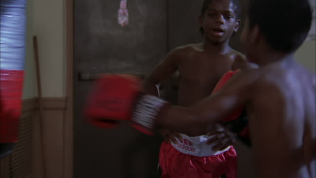 boy wearing large red gloves hits punching bag as other boy advises, illinois, chicago available in hd. - comment box stock videos & royalty-free footage