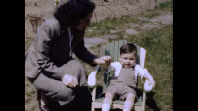 boy wearing overalls and oxford shoes sits in a child's adirondack chair in a yard. - アディロンダックチェア点の映像素材/bロール