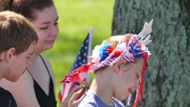 a boy wearing patriotic items on his head amuses himself by sticking his tongue out during memorial day ceremonies at valhalla memory gardens may 29... - veterans of foreign wars of the united states stock videos & royalty-free footage