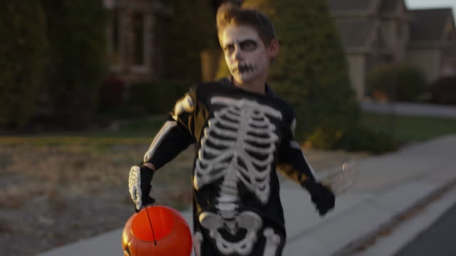 Boy wearing skeleton costume running in neighborhood on Halloween / Cedar Hills, Utah, United States