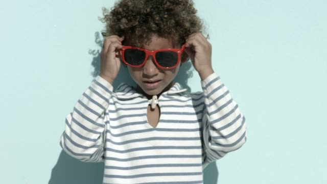 boy wearing sunglasses against blue background - man made object stock videos & royalty-free footage