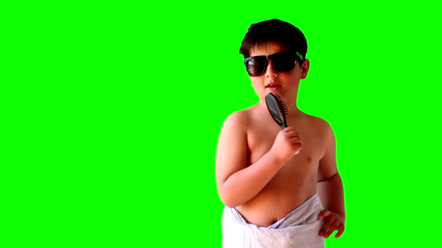 boy wearing sunglasses and a towel singing in a comb - wearing a towel stock videos & royalty-free footage