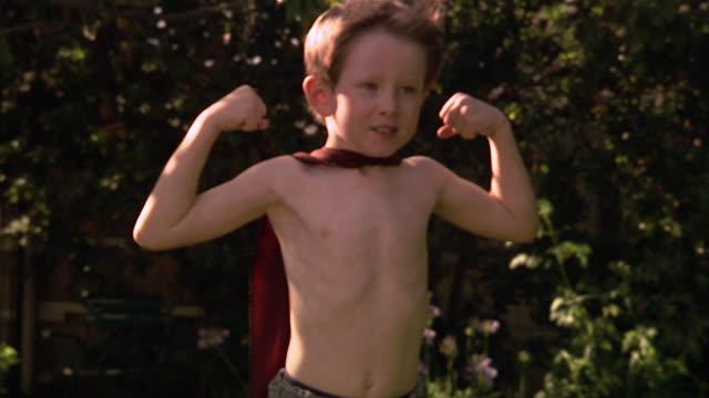 vídeos y material grabado en eventos de stock de slo mo ms boy wearing superhero cape and flexing muscles / los angeles, california, usa - flexionar los músculos