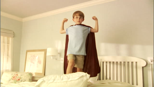MS, Boy (6-7) wearing superhero cape flexing muscles on bed, portrait