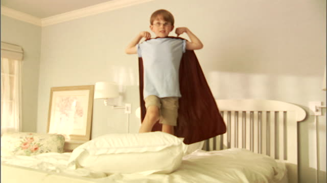 ms, boy (6-7) wearing superhero cape flexing muscles on bed, portrait - flexing muscles stock videos and b-roll footage