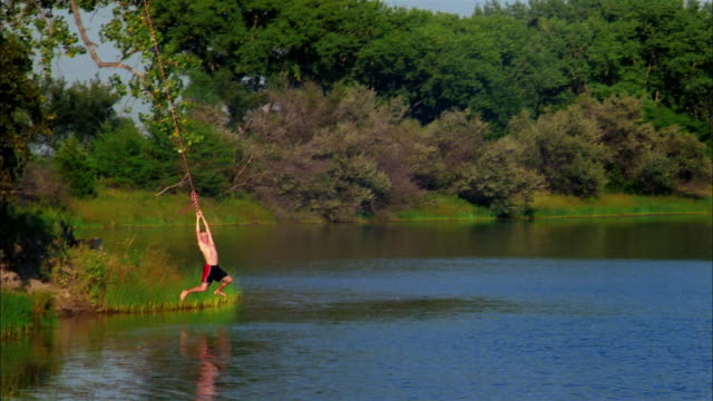 vídeos de stock e filmes b-roll de a boy wearing swim trunks swings on a rope and jumps into a lake. - corda