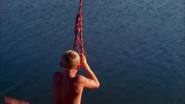 a boy wearing swim trunks swings on a rope and jumps into a lake. - rope stock videos & royalty-free footage