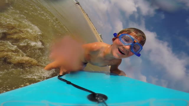A boy wears goggles while going body boarding at the beach. - Slow Motion