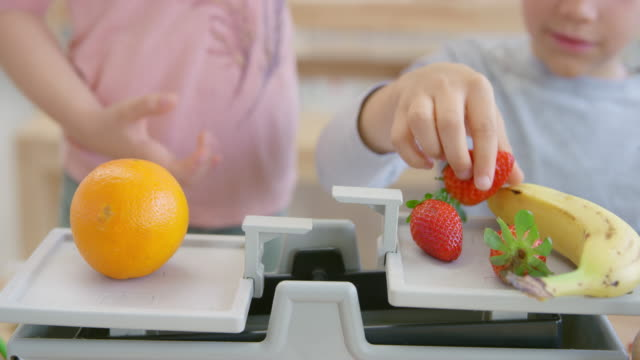ld boy weighing fruit in the classroom with a balance scale - man made object stock videos & royalty-free footage