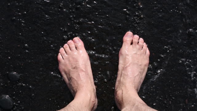 boy wetting his feet on the beach with a wave - black sand stock videos & royalty-free footage