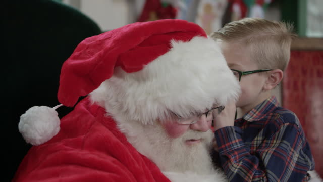 boy whispers into santa's ear - nordpolen bildbanksvideor och videomaterial från bakom kulisserna