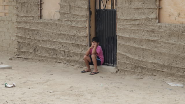 a boy who is wearing a pink shirt is sitting in front of a self made hut the road in front of him is dry and sandy in a small village near sullana... - pink shirt stock videos and b-roll footage