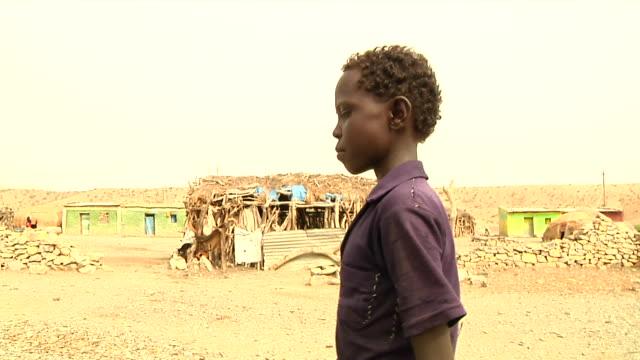 boy who went through teeth ritual walking through village - äthiopien stock-videos und b-roll-filmmaterial