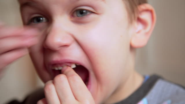 boy wiggle a loose tooth - human tongue stock videos & royalty-free footage
