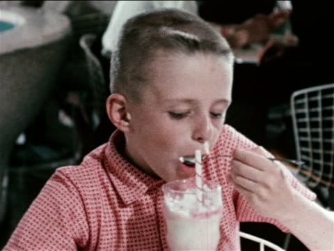 stockvideo's en b-roll-footage met 1963 boy with crew cut eating ice cream soda + smiling / industrial - 1963