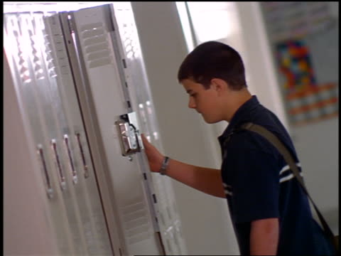 stockvideo's en b-roll-footage met canted boy with cropped hair opening, closing + punching locker with fist in high school hallway - lockerkast