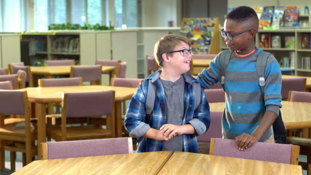 boy with down syndrome and friend in elementary school - sindrome di down video stock e b–roll